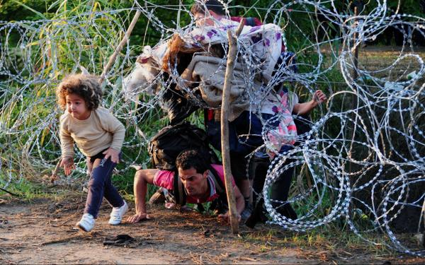 Syrian refugees crossing a similar fence on the Bulgarian border with Turkey. (AP)