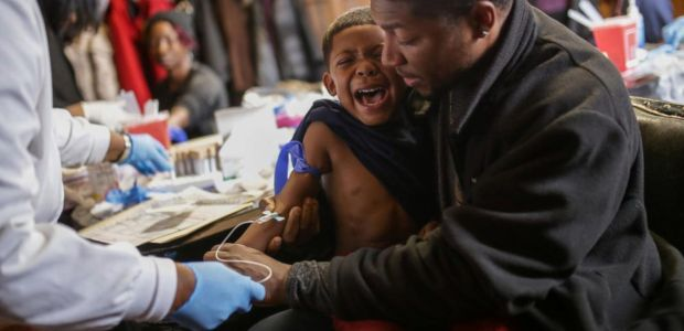 Flint man consoling his child as the boy gets his blood drawn to check blood lead levels. (ABC News)