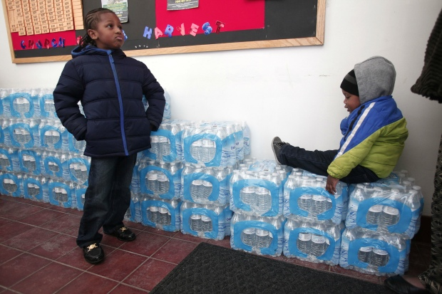 Flint children playing around crates of donated water bottles. (Bill Pugliano/Getty Images)