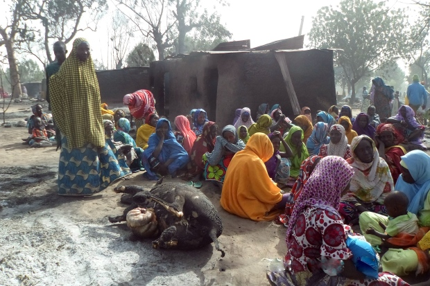 Women sitting next to a burnt cow carcass in the wake of the Boko Haram attack on Dalori village. (AFP/Getty Images)