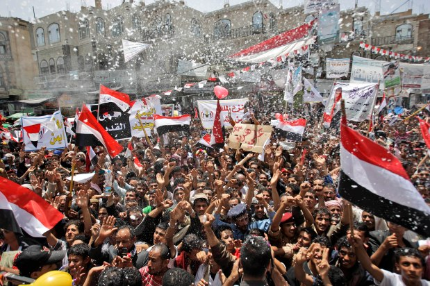 Anti-government protesters spray foam and wave their national flags as they celebrate President Ali Abdullah Saleh's departure to Saudi Arabia, in Sanaa, Yemen, Sunday, June 5, 2011. Thousands of protesters are dancing and singing in the Yemeni capital Sana'a after the country's authoritarian leader flew to Saudi Arabia to receive medical treatment for wounds he suffered in a rocket attack on his compound. (AP Photo/Hani Mohammed)