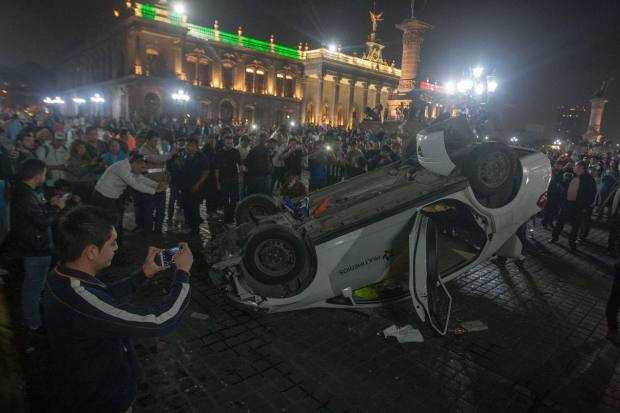 Demonstrators surround an overturned car outside of the Governor's Palace in Monterrey, Nuevo Leon Thursday night. (Julio Cesar Aguilar/AFP/Getty Images)