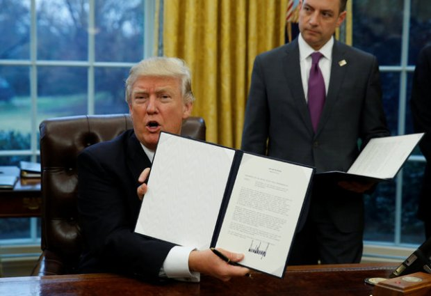 President Trump showing off the executive order to withdraw the United States from the Trans Pacific Partnership. (Reuters/Kevin Lamarque)